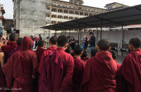 Tour members performing some tunes for young monks at a monastery